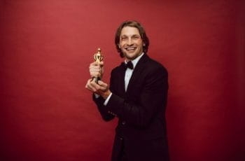 A smiling man in a black suit holding a gold award statue.