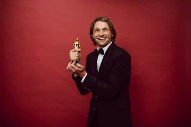 Seorang pria tersenyum dalam setelan hitam memegang patung penghargaan emas.