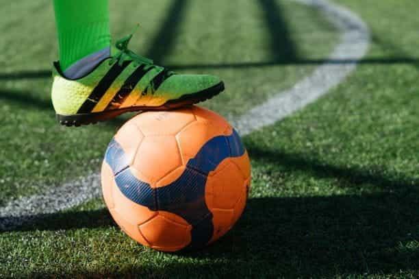 Seorang pesepakbola dengan kaus kaki hijau dan sepatu bot dengan kaki mereka di atas bola oranye.