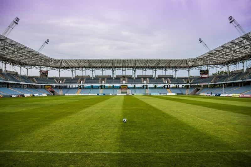 Lapangan sepak bola kosong di stadion sepak bola, dengan satu sepak bola duduk sendirian di rumput.