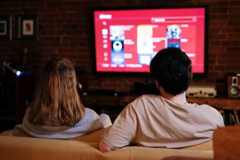 Sepasang suami istri menonton TV, duduk di sofa di ruang tamu.