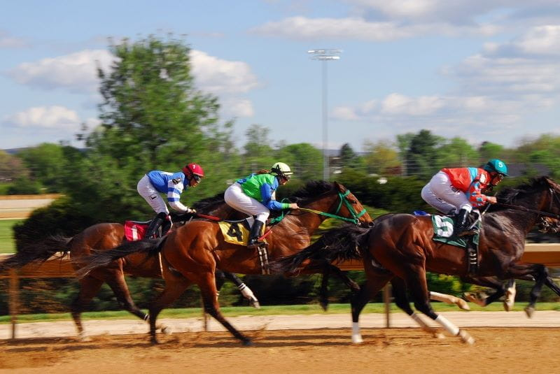 Tiga joki berlomba kuda mereka selama pacuan kuda.