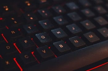 A close-up of a keyboard with red lighting underneath the keys.