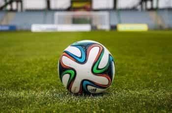 A football on a grass pitch.
