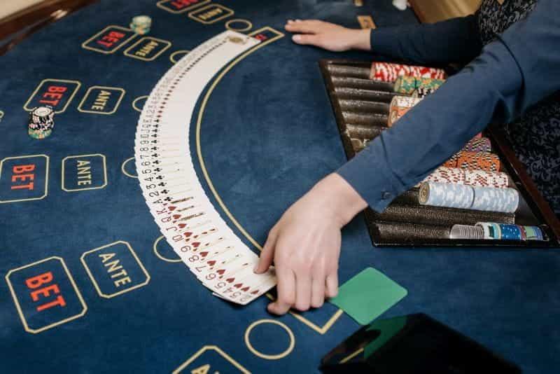 Seorang bandar kasino membagikan setumpuk kartu remi, dengan chip poker.