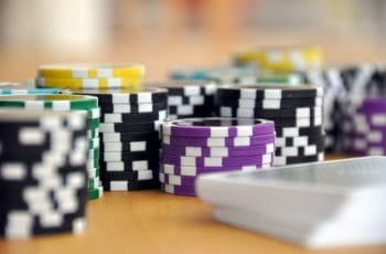 Black, purple and yellow poker chips next to a deck of playing cards.