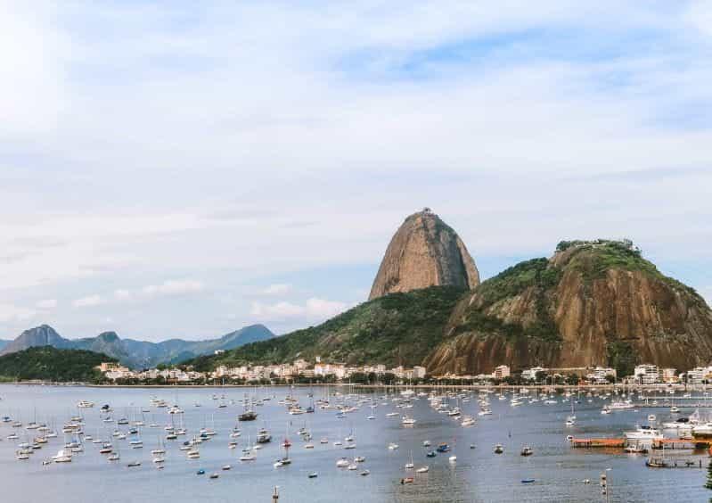 Pegunungan di Brasil di tepi laut, dengan perahu dan bangunan.