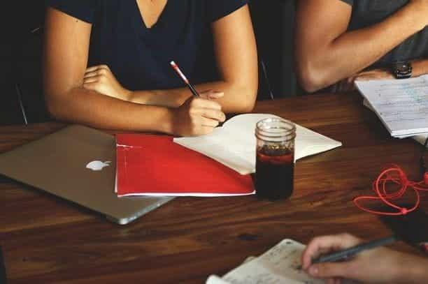 Seseorang yang duduk di meja selama rapat di depan laptop dan dokumen tertutup.