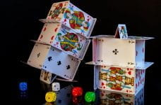 Playing cards stacked on top of one another in intricate house of cards arrangements.