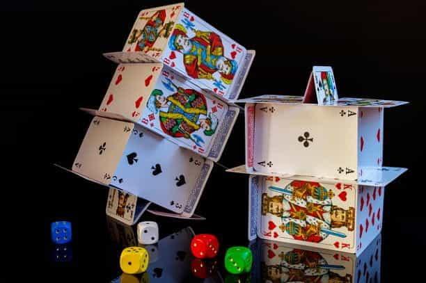 Bermain kartu yang ditumpuk di atas satu sama lain dalam pengaturan rumah kartu yang rumit.