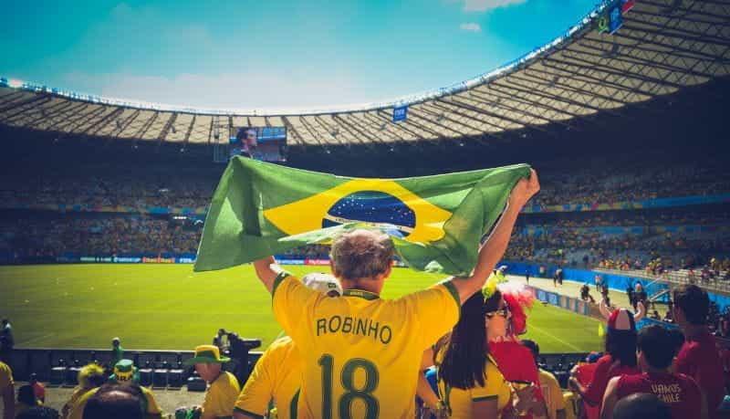 Seorang penggemar sepak bola Brasil mengangkat bendera di stadion sepak bola.