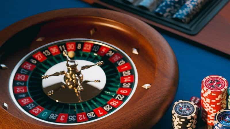 Meja roulette klasik di kasino dengan setumpuk chip di sampingnya.