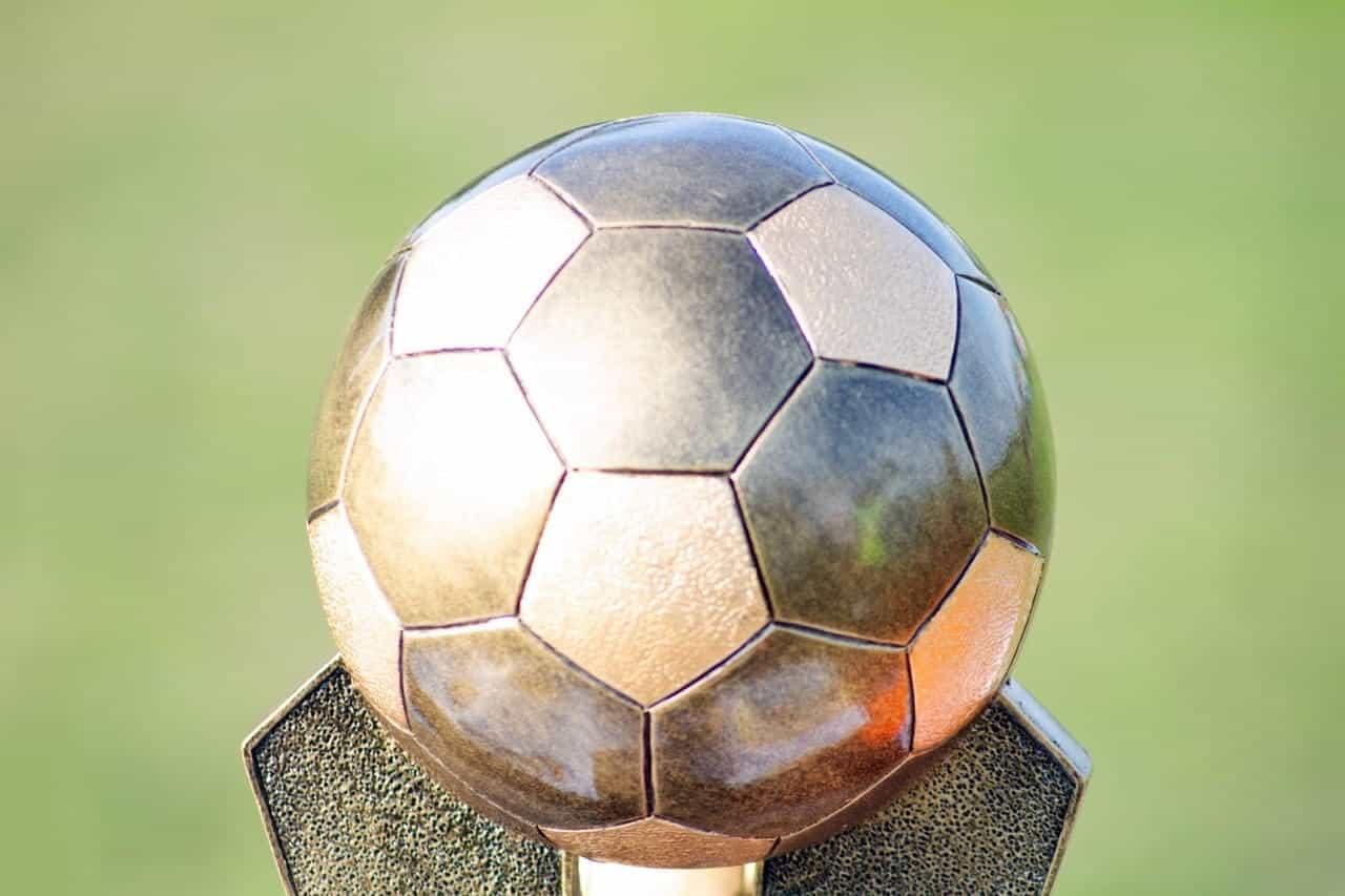 Bola sepak perak di bagian atas piala ada di tengah.