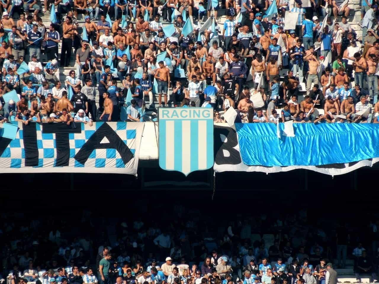 Fans yang mengenakan warna bendera tradisional Argentina memenuhi arena yang ramai untuk menonton pertandingan sepak bola.