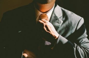 A person in a suit straightening or adjusting his tie.