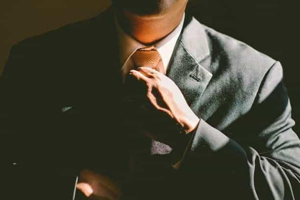 Seseorang dalam setelan jas meluruskan atau menyesuaikan dasinya.