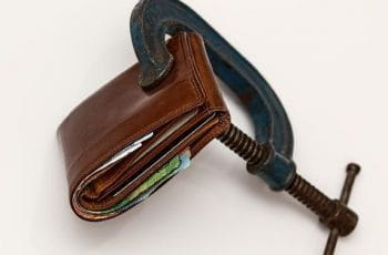 A brown wallet being squeezed tight with a clamp.