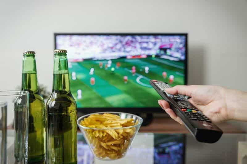 Sebuah tangan memegang remote menunjuk ke TV yang menayangkan pertandingan sepak bola, dengan botol bir dan semangkuk keripik.