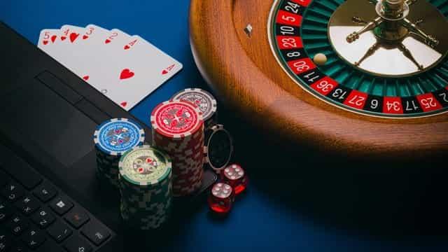 Sebuah laptop di sebelah roda roulette, dengan kartu remi, chip poker, dan dadu merah.