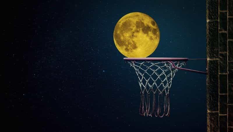 Sebuah ring basket jalanan pada malam hari, dengan bulan kuning purnama di belakangnya.