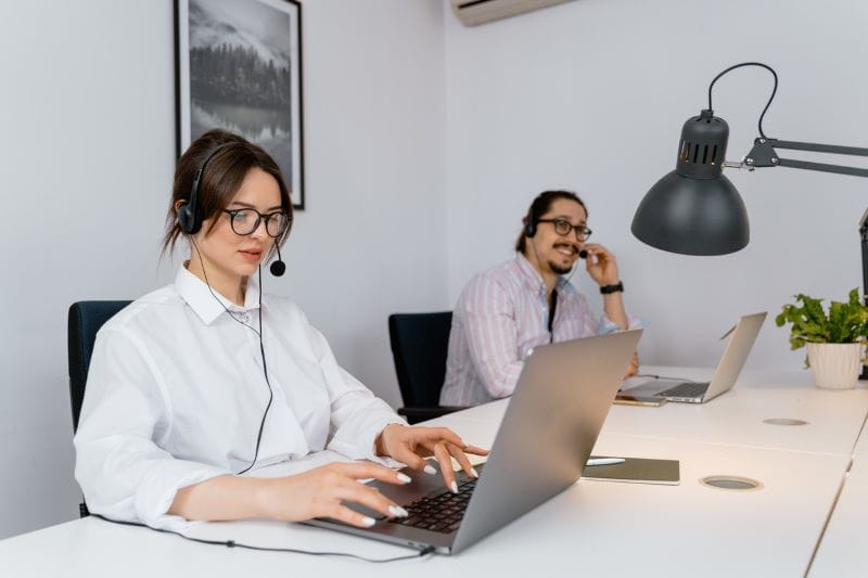 Dua orang memakai headset, bekerja pada laptop di kantor.