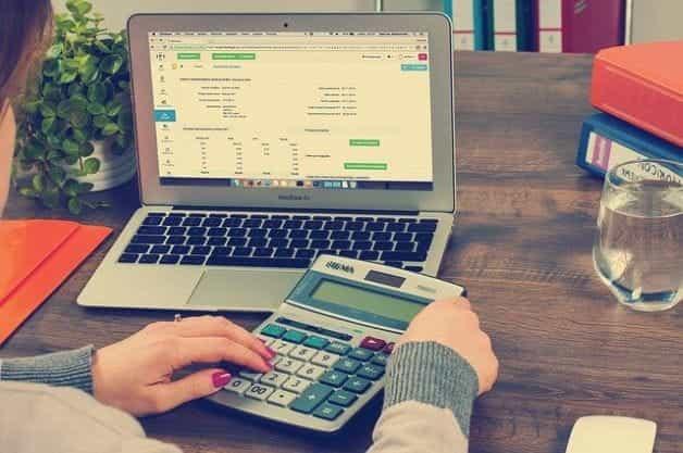 Seorang wanita duduk di depan spreadsheet di laptop dengan kalkulator di tangannya.