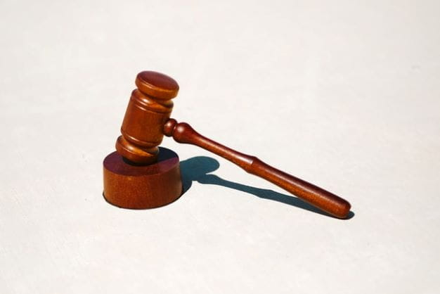Palu hakim diletakkan di atas permukaan putih.