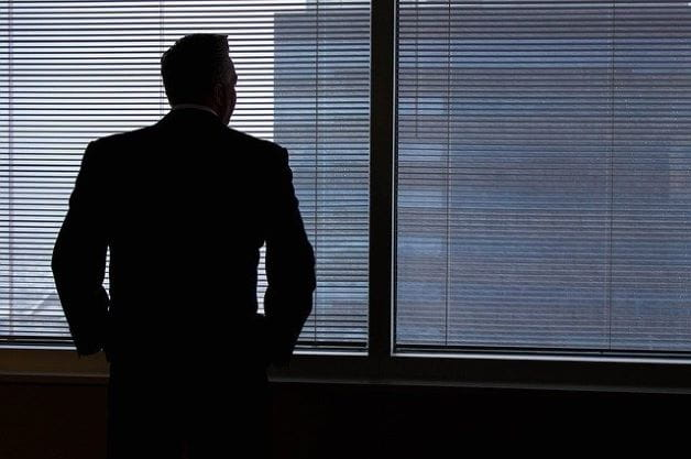 Seorang pengusaha berdiri di depan jendela dengan bayangan digambar.