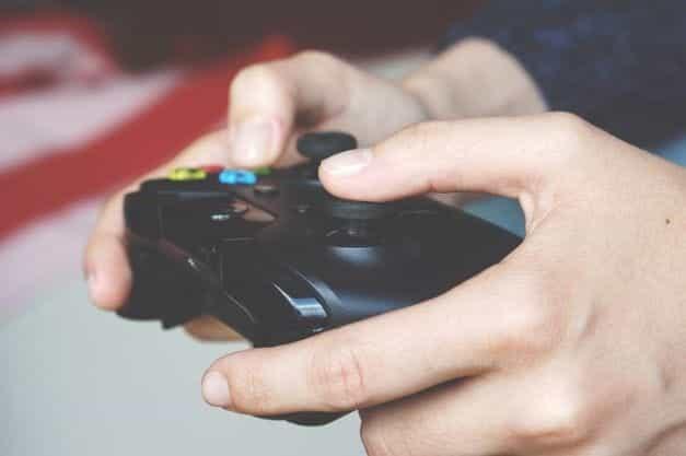 Tangan memegang pengontrol video game.