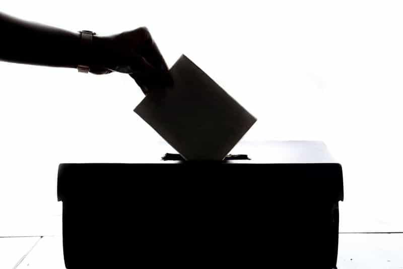 Sebuah tangan siluet menempatkan suara ke dalam kotak suara.