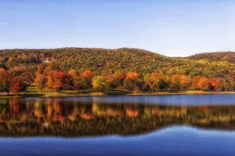Kolam Squantz di pedesaan Connecticut, dengan perbukitan dan pepohonan di latar belakang.