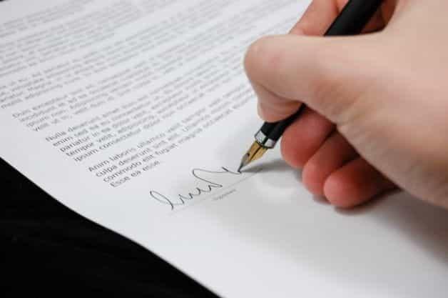 Sebuah tangan menandatangani dokumen hukum dengan pena.