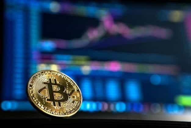 Bitcoin emas duduk di depan monitor dengan grafik data.