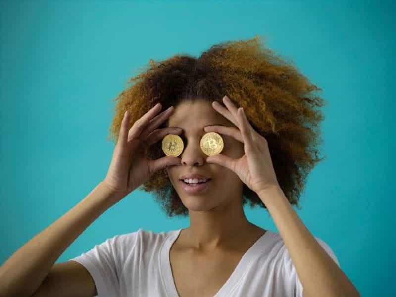 Seorang wanita memegang Bitcoin emas di depan matanya.