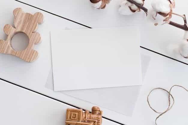 Sebuah amplop putih kosong tergeletak di atas meja yang dikelilingi oleh pernak-pernik.