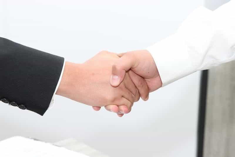 Dua tangan berjabat tangan untuk menandai penutupan merger bisnis.