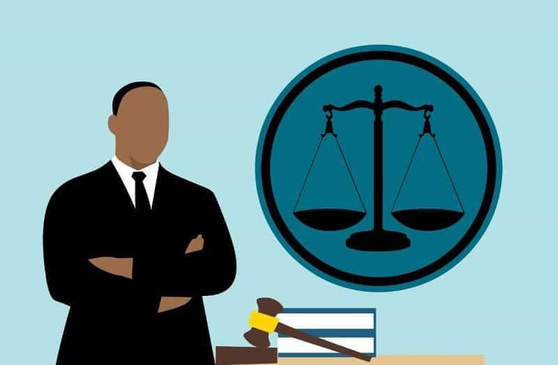 Seorang hakim berdiri di depan palu, tumpukan buku, dan timbangan keadilan.