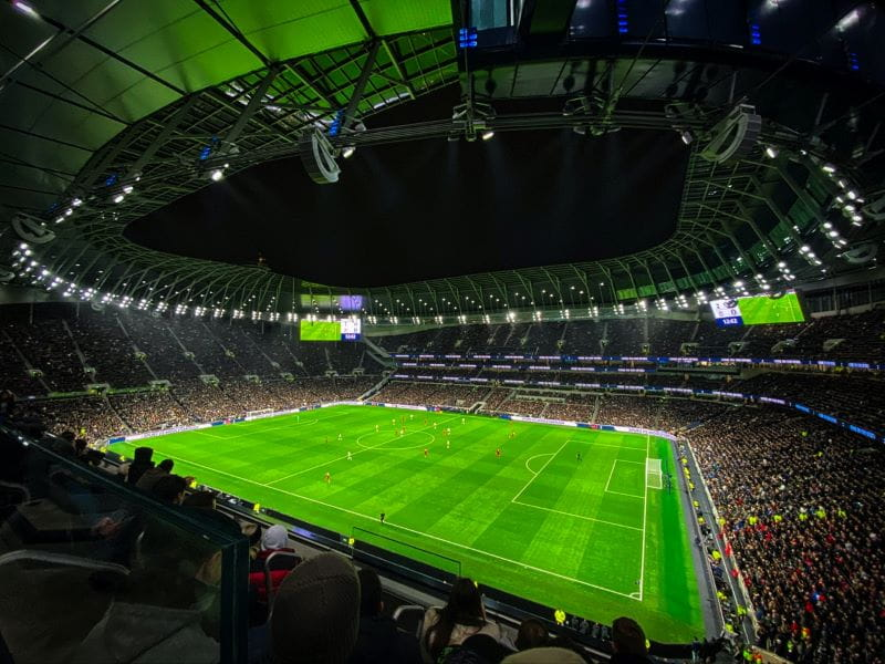 Lapangan sepak bola hijau di stadion sibuk yang penuh dengan penonton.