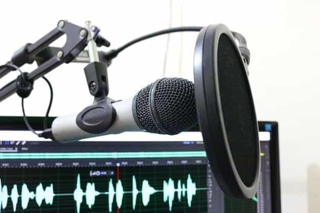 Mikrofon dengan pop guard di depan monitor dengan gelombang suara di atasnya.