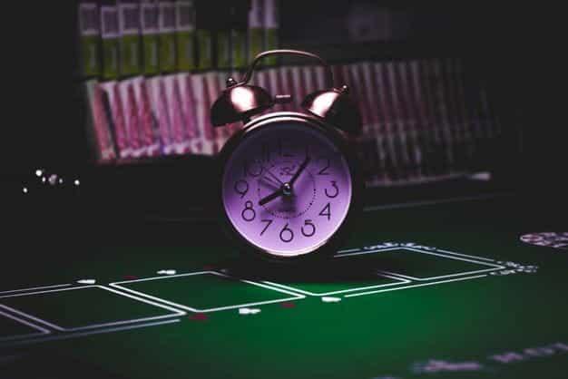 Jam alarm lonceng perak kuno duduk di atas meja poker kosong.