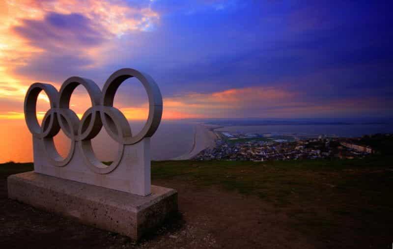 Patung cincin Olimpiade di atas kota di tepi laut.