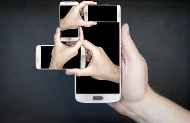 Kolase tangan memegang smartphone besar dengan layar menghadap ke atas.