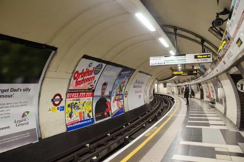 Stasiun Tube Bawah Tanah London, dengan iklan dan orang-orang menunggu kereta.
