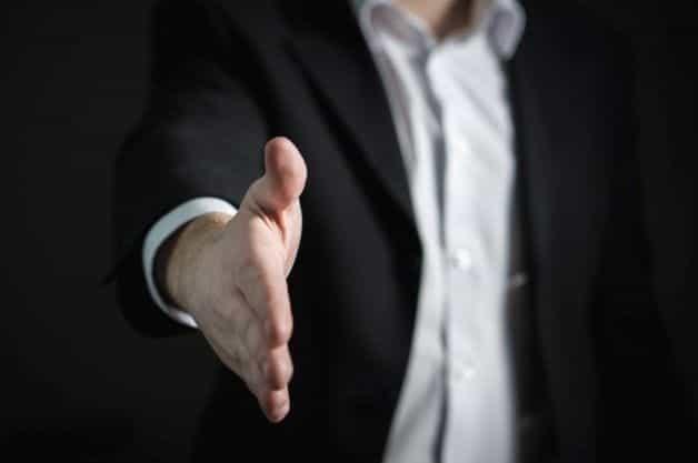 Seorang pria dalam setelan bisnis dengan tangan terentang.
