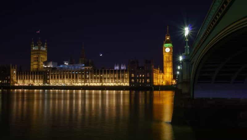 Gedung Parlemen menyala di malam hari, di seberang sungai Thames.