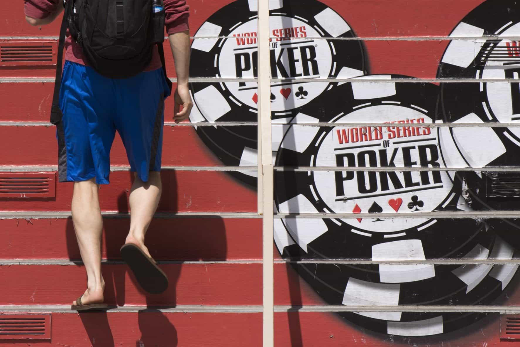 Seorang pria berjalan menaiki tangga, yang memiliki logo World Series of Poker terlukis di atasnya.