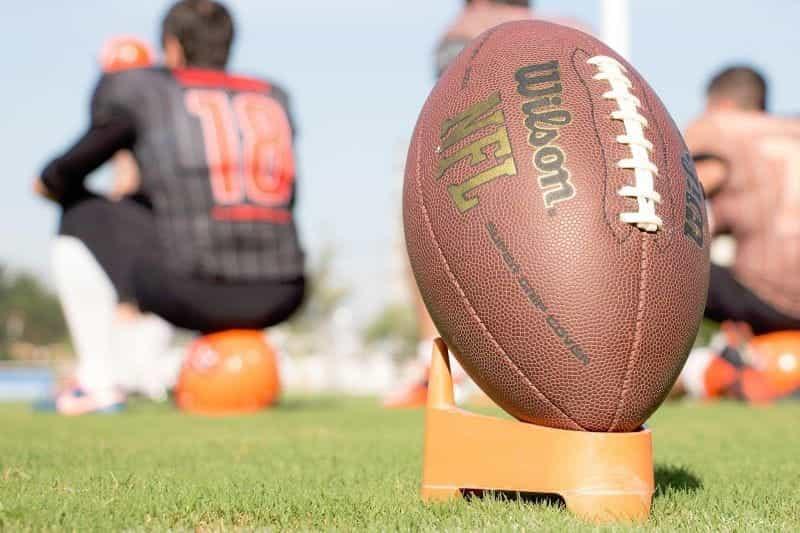 Sebuah American football bertengger di sebuah stand siap untuk ditendang.