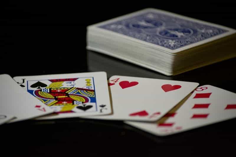 Setumpuk kartu remi, dengan tangan terbentang di depannya.