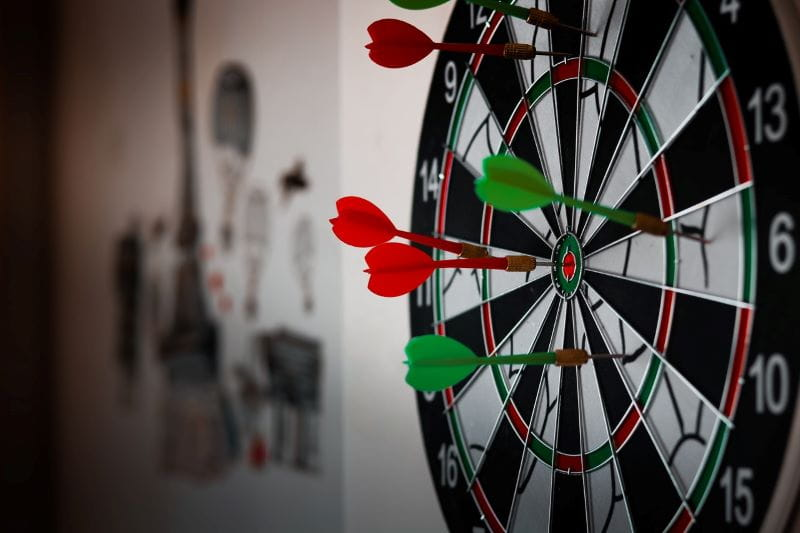 Papan dart dengan anak panah hijau dan merah.