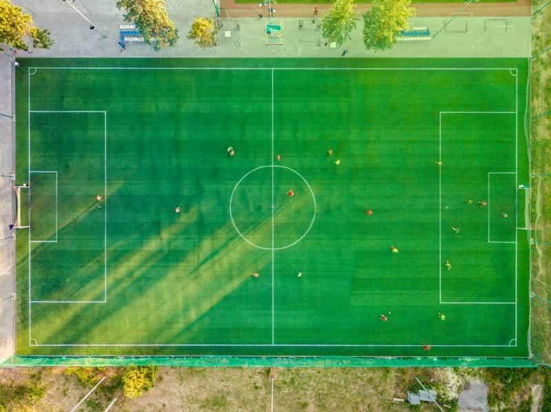 Lapangan sepak bola hijau dengan pemain dari atas.